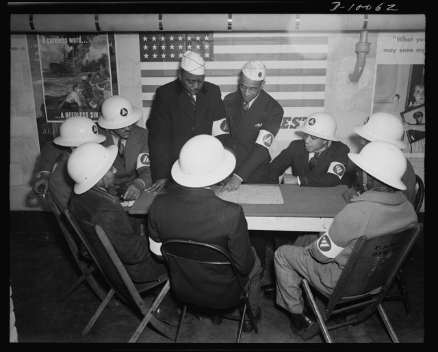 Office of Civilian Defense workers help protect nation's capital. Air raid wardens at a sector meeting in Washington, D.C., discuss the zones they control during a practice air raid. The air raid warden, key man of the civilian defense organization, must be well known to the people of his sector. It is his job to clear the streets, see that people take proper cover, prevent panic and summon aid promptly when it is needed