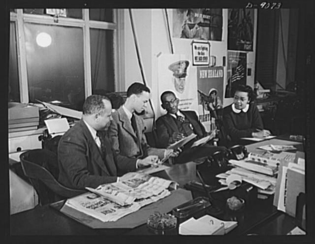 Office of War Information news bureau. Besides supplying war news from all government agencies to 240 Negro papers each week, Ted Poston, editor of the OWI's Negro desk in Washington, selects picture sequences of special interest to the Negro press. He is shown working with photographer Roger Smith and assistant William Clark, and Harriette Easterlin