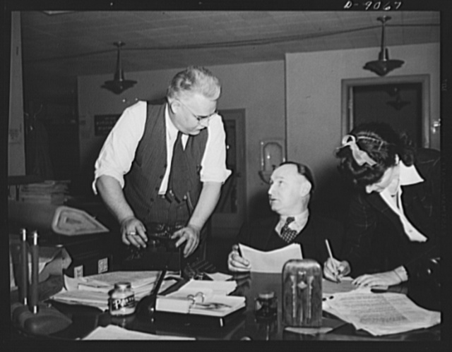 Office of War Information News Bureau. Elmer Roessner, chief of the general news desk, talks over a news release with Sutherland Denlinger. The chief of the general news desk keep an eye on all the news that goes out of the news bureau to the seventy- five correspondents in the Office of War Information's Washington press room, to all specialized news media, and to the New York and San Francisco offices of OWI where it is prepared for shortwave radio broadcasts and cable transmission overseas