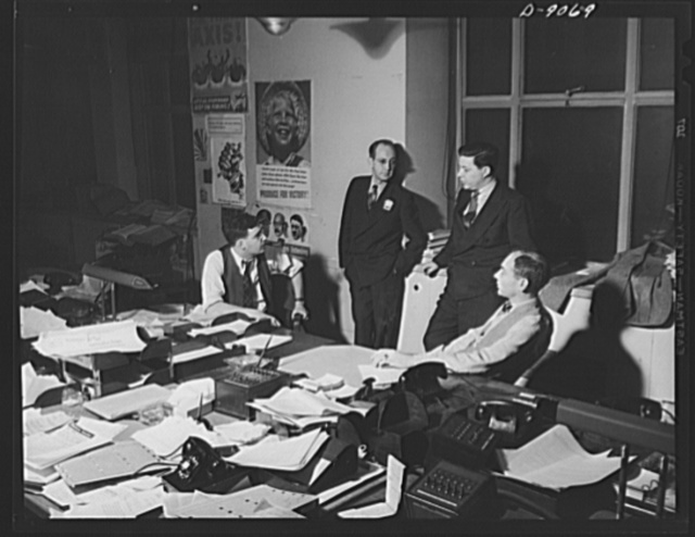 Office of War Information News Bureau. George McMillan, assistant chief of the OWI news bureau, talks over a program for a series of releases on inflation with Herb Plummer, standing at his right, Jack Durham and Joe Polakoff. When a series of releases is planned, the news bureau schedules them, often including plans for releases for rural papers, trade papers, house organs, etc., as well as the daily press