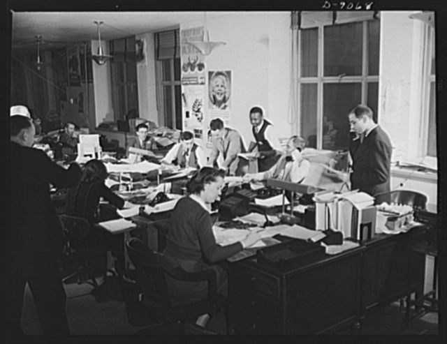 Office of War Information News Bureau. Like a busy city desk, the domestic news desk concentrates on getting releases out to meet deadlines of its press room's seventy-five to one hundred correspondents. After they reach the Office of War Imformation, each of the fifty or more daily releases are passed on to Jack Durham by Hy Aronstam, news desk chief, standing at phone. Durham sees that releases agree with policies of all government agencies involved, prevents contradictory statements from going out. Pipe-lighting Joe Polakoff copy reads and edits releases