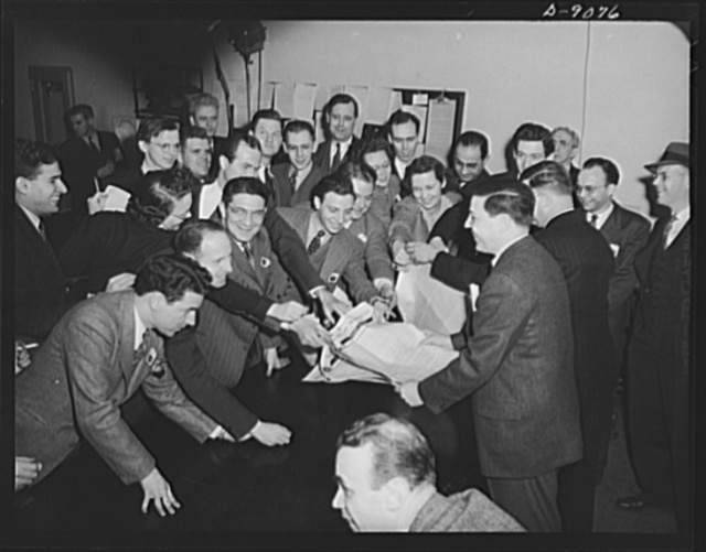 Office of War Information news bureau. Smiling unnaturally, some of the newsmen in OWI busy press room grab for a handout giving point values on canned goods from George (fatso) McMillan, assistant chief of the news bureau. McMillan has tried to make the news bureau work like a newspaper, has a reputation for understanding the newsman's side of government information