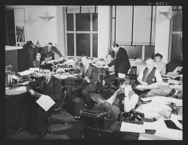 """Office of War Information news bureau. These OWI reporters work six days a week on stories for both domestic and overseas use. In the course of a week most of them turn out a list of assignments as long as a cub reporter's. Examples of the variety of stories done: """"Roundup on wartime transportation,"""" """"Industrial feeding program started in war plants,"""" """"U.S. Army heroes of Greek descent,"""" """"How to get your tires recapped."""" Stories for domestic release go to the chief of the general news desk. Ken Stewart, chief of the foreign desk, reviews all overseas assignments"""