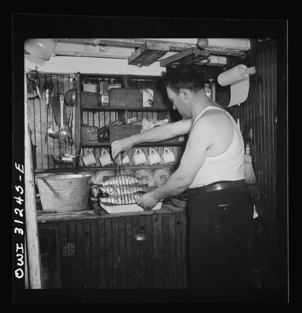 On board the Alden out of Gloucester, Massachusetts. Men lashing the seining boat to the side of the big ship, while another pumps all the water from the boat floor. This finished, they were ready to start for home with a catch of 70,000 pounds of mackerel