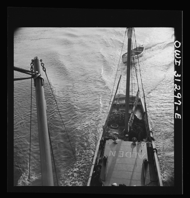 On board the fishing boat Alden out of Gloucester, Massachusetts. A scene at sea showing the mother ship towing a small dory