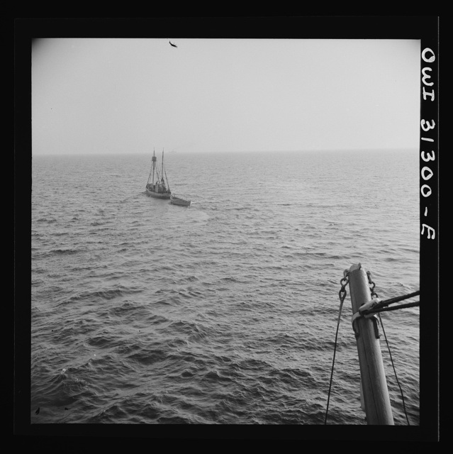 On board the fishing boat Alden out of Gloucester, Massachusetts. Fishing schooner towing a dory off the New England coast