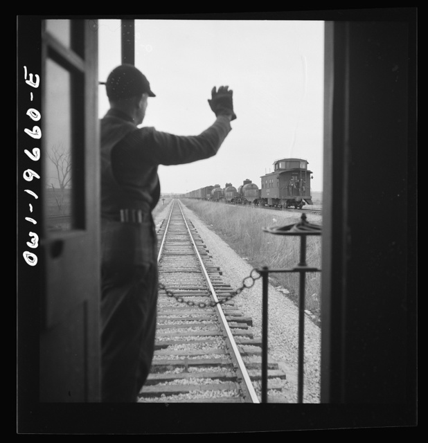 On the Atchison, Topeka, and Santa Fe Railroad between Marceline, Missouri and Argentine, Kansas. Brakemen exchanging highball signs. When two trains pass one another, the brakeman watch the other train for signs of hot boxes or other damage. If all is well, the highball sign is given. If not, other signals, to indicate the type of trouble, are used
