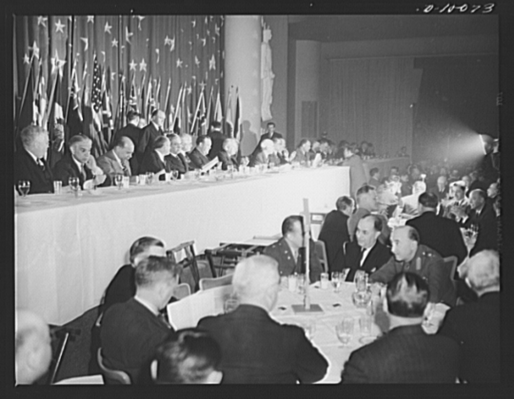 On the dais at luncheon in honor of second anniversary of lend-lease, held March 11, 1943, at the Hotel Statler, Washington, D. C. Left to right: minister of the Union of South Africa, Ralph William Close; ambassador of Greece, Cimon Diamantopoulos; ambassador of Panama, Senor Don Ernesto Jean Guardia; ambassador of Mexico, Senor Dr. Don Francisco Castillo Najera; Secretary of Commerce Jesse Jones; Norwegian foreign minister, Trygze Lie; ambassador of Russia, Maxim Litvinov; Vice-President Henry A. Wallace; Lend-lease administrator Edward R. Stettinius, Jr.; Chinese foreign minister T.V. Soong; British ambassador Lord Halifax; ambassador of Belgium, Count Robert van der Straten-Ponthoz; Secretary of Agriculture Claude A. Wickard; ambassador of Poland, Jan Ciechanowski; ambassador of Norway, Wilhelm Munthe de Morgenstiderne; Senator Arthur Capper of Kansas; minister of Guatemala, Senor Dr. Adrian Recinos; minister of Czechoslovakia, Vladimir Hurban; Representative Sol Bloom, chairman of the House Committee on Foreign Affairs; minister of Honduras, Senor Dr. Don Julian R. Caceres; minister of Costa Rica, Senor Dr. Don Luis Fernandez; minister of Luxembourg, Hugues Le Gallais; the Philippine Resident Commissioner Joaquin M. Elizalde