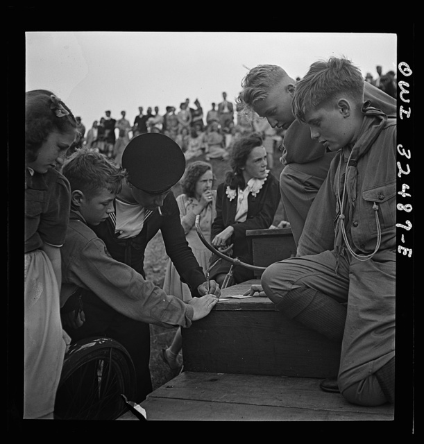 Oswego, New York. A Greek sailor whose right arm has been disabled in the war writing his autograph with his left hand for a boy scout on Flag Day during United Nations week