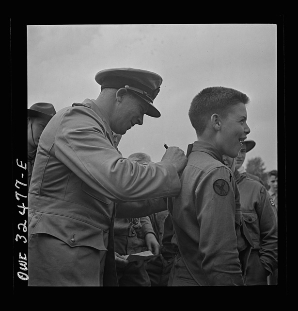 Oswego, New York. A Norwegian naval officer writing his autograph for a boy scout during United Nations week