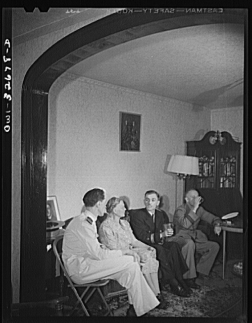 Oswego, New York. Canadian flight commander and Polish naval officers visiting in the home of a Polish-American family