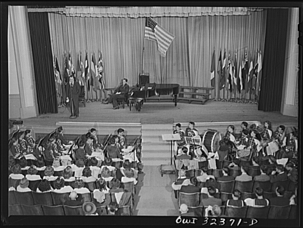 Oswego, New York. Howard Fast, author of Citizen Tom Paine, addressing the high school. United Nations flags are on the stage during United Nations week