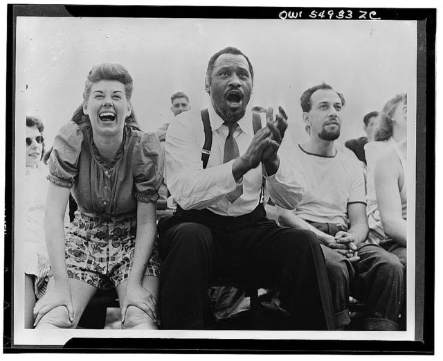 [Paul Robeson and Jose Ferrer watching a softball game with other members of Othello production, Central Park, New York City]