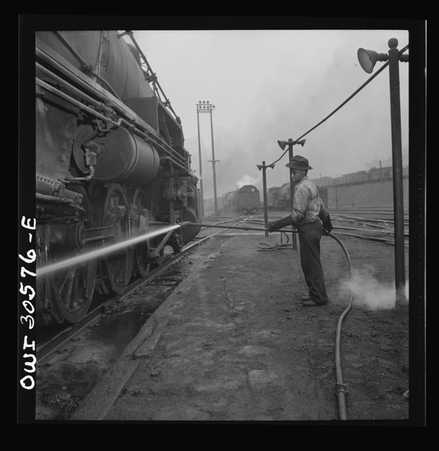 Pitcairn, Pennsylvania. Mrs. Bernice Stevens of Braddock, Pennsylvania, mother of one child, employed in the engine house of the Pennsylvania Railroad, earns fifty-eight cents per hour. She is cleaning a locomotive with a high pressure nozzle. Mrs. Stevens' husband is in the U.S. Army