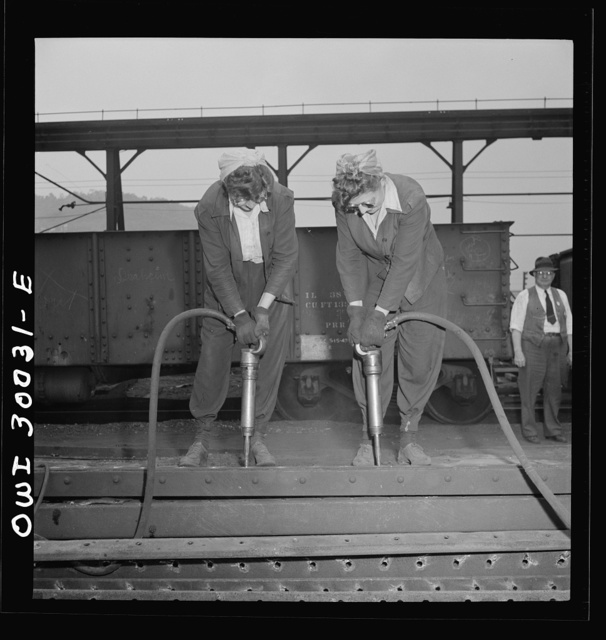 Pitcairn, Pennsylvania. Twins Amy and Mary Rose Lindich, twenty-one, employed at the Pennsylvania Railroad as car repairmen helpers, earning seventy-two cents per hour. They reside in Jeanette, Pennsylvania, and carpool with fellow workers. Dismantling sides of the old hopper cars