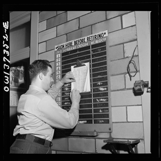Pittsburgh, Pennsylvania. A Greyhound bus driver signing in for a bed at the dormitory in the garage. A porter checks the list and calls the drivers in time for their runs