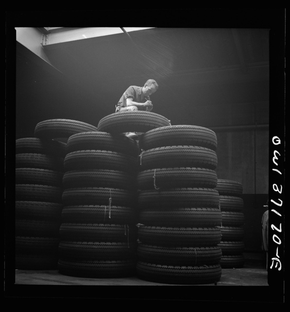 Pittsburgh, Pennsylvania. Checking brand numbers on new tires at the Greyhound garage