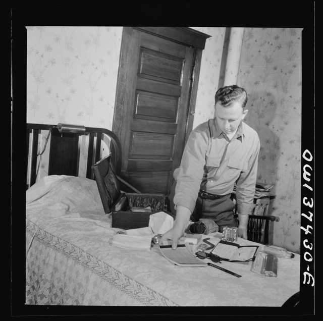 Pittsburgh, Pennsylvania. Clem Carson, a Greyhound bus driver, packing the suitcase which he takes with him on a run