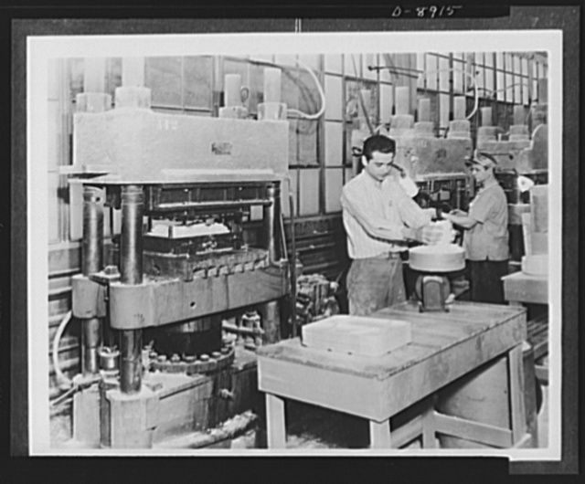 Plastic tableware for the Navy. Durable plastic tableware, designed to replace china and aluminum dishes used on naval vessels, is made of impregnated fabric molding material. Here the operator weighs out the correct amount of material for a molding operation as shown in the press at the left