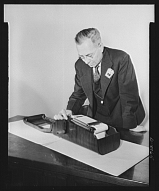 Plywood autographic registers. A war model autographic register made entirely of plywood is inspected by Nathaniel G. Burleigh, director of Service Equipment Division of War Production Board (WPB). The registers are used by commercial firms in writing duplicate orders, by receptionists in filling out admission passes to office buildings, and for many other purposes