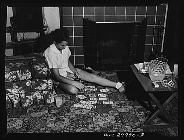 Point Pleasant, West Virginia. Nancy Fergusen playing a game of solitaire. The town is practically depopulated of young men