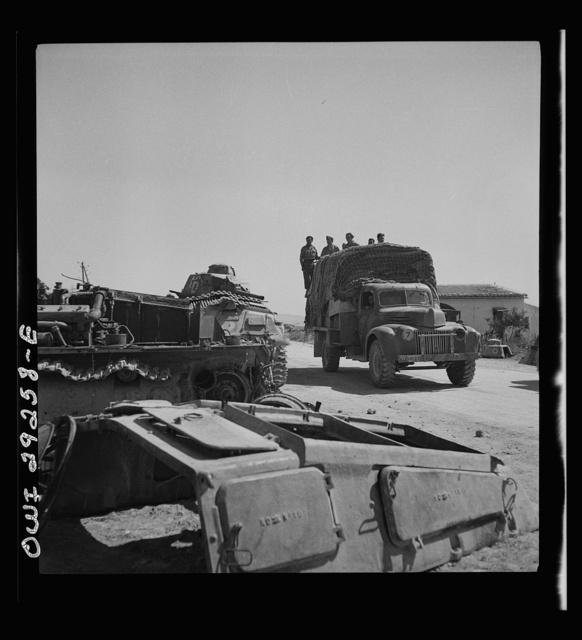 Porto Farina, Tunisia. Allied truck passing wrecked German tanks