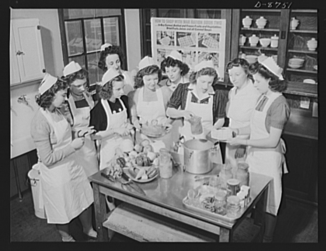 Preparation for point rationing. A home economics class of the McKinley High School, Washington, D.C., gets a practical lesson in home canning of fruits and vegetables, looking toward supplementing the limited allowance of canned foods available to holders of war ration book two. Mrs. Elouise Gummer, their teacher, explains the use of pressure cooker for canning