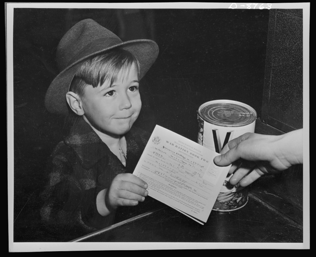 Preparation for point rationing. An eager school boy gets his first experience in using war ration book two. With many parents engaged in war work, children are being taught the facts of point rationing for helping out in family marketing