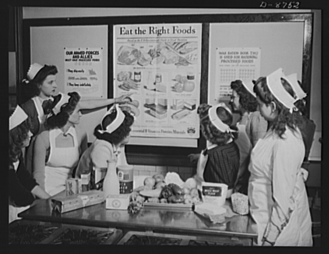 "Preparation for point rationing. ""Know your points and your food values"" is the lesson being taught these home economics pupils in the McKinley High School, Washington, D.C.  A student indicates the importance of fresh fruits and vegetables in conserving rationing points"