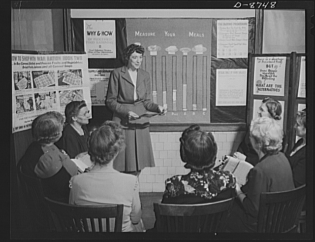 Preparation for point rationing. Miss Elizabeth Law, who teaches an adult homemaking class at Mckinley High School, Washington, D.C., explains the use of war ration book two to a group of homemakers at the school. The relationship of balanced diets to point-rationed foods is taught to adult classes open to all D.C. homemakers