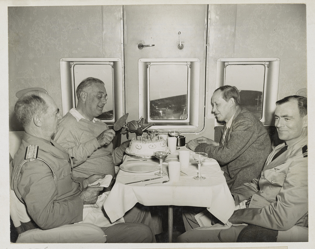 President's trip abroad meeting with Churchill. President Roosevelt is about to cut into birthday cake. Enroute in a big plane from Trinidad to Miami on his 61st birthday anniversary, he had to forego his customary personal address to celebrate at birthday balls throughout the United States for the benefit of infantile paralysis suffers. At his right is his chief military advisor, Admiral William D. Leahy. Looking on with deep interest from the other side of the table is Harry L. Hopkins. Lieutenant Cone, captain of the plane, is at Hopkins' left