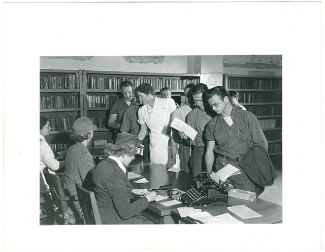 [Prisoners at in the library at San Quentin doing paperwork with women in medical and military uniforms]