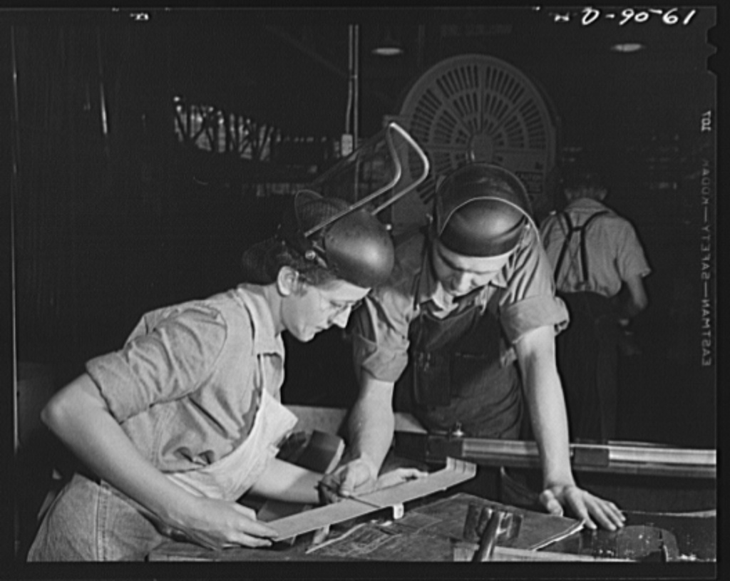"""Production. A-31 (""""Vengeance"""") dive bombers. Checking part to blueprint. Here a pair of factory workers check the blueprint with a part which will go into the """"Vengeance"""" dive bombers made at Vultee's Nashville Division. The """"Vengeance"""" (A-31) was originally designed for the French. It was later adopted by the RAF (Royal Air Force) and still later by the U.S. Army Air Forces. It is a single-engine, low-wing plane, carrying a crew of two men and having six machine guns of varying calibers"""