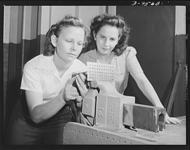 """Production. A-31 (""""Vengeance"""") dive bombers. Drilling education. These two girls are learning to drill rivet holes before being put to work on the """"Vengeance"""" dive bombers made at the Nashville Division of Vultee Aircraft Inc. The """"Vengeance"""" (A-31) was originally designed for the French. It was later adopted by the RAF (Royal Air Force) and still later by the U.S. Army Air Forces. It is a single-engine, low-wing plane, carrying a crew of two men and having six machine guns of varying calibers"""