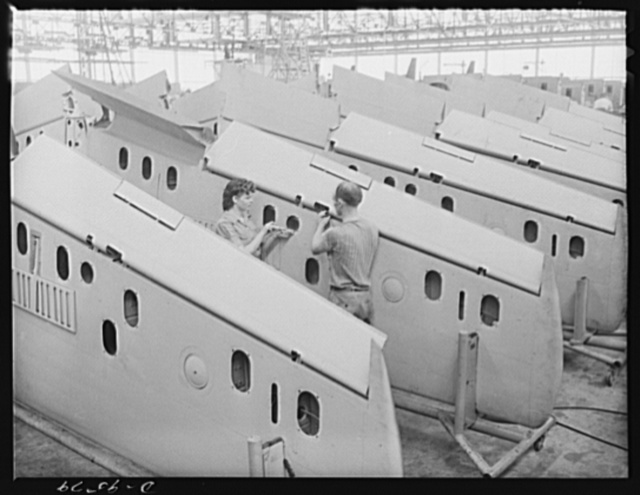 """Production. A-31 (""""Vengeance"""") dive bombers. Flap installation. This pair of workers are adjusting a flap installation on the outer wings upon arrival from the sub-contractor's plane prior to installation on the Vultee """"Vengeance"""" dive bombers manufactured at Vultee's Nashville Division. The """"Vengeance"""" (A-31) was originally designed for the French. It was later adopted by the RAF (Royal Air Force) and still later by the U.S. Army Air Forces. It is a single-engine, low-wing plane, carrying a crew of two men and having six machine guns of varying calibers"""