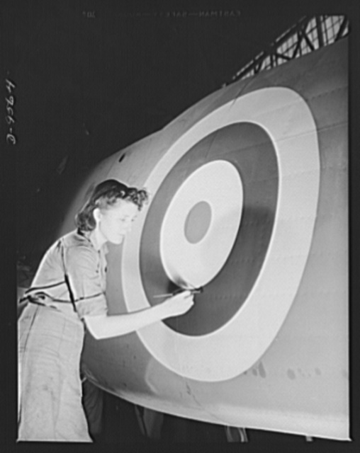 "Production. A-31 (""Vengeance"") dive bombers. Insignia touch-up. Woman worker is shown retouching the British insignia on the fuselage of a ""Vengeance"" dive bomber made at Vultee's Nashville Division. The ""Vengeance"" (A-31) was originally designed for the French. It was later adopted by the RAF (Royal Air Force) and still later by the U.S. Army Air Forces. It is a single-engine, low-wing plane, carrying a crew of two men and having six machine guns of varying calibers"