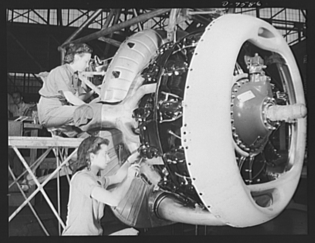 """Production. A-31 (""""Vengeance"""") dive bombers. Installation of exhaust-collector ring. Two women employees at the Nashville Division of Vultee Aircraft Inc. are shown installing the exhaust-collector ring on a motor which will go into a Vultee """"Vengeance"""" dive bomber. The """"Vengeance"""" (A-31) was originally designed for the French. It was later adopted by the RAF (Royal Air Force) and still later by the U.S. Army Air Forces. It is a single-engine, low-wing plane, carrying a crew of two men and having six machine guns of varying calibers"""