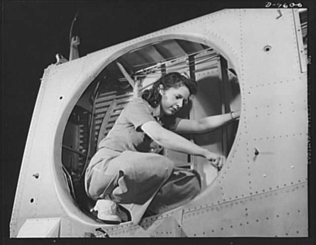 """Production. A-31 (""""Vengeance"""") dive bombers. Landing gear installation. This woman worker at Vultee-Nashville is shown making final adjustments in the wheel well of an inner wing before installation of the landing gear. This is one of the numerous assembly operations in connection with the mass production of Vultee """"Vengeance"""" dive bombers. The """"Vengeance"""" (A-31) was originally designed for the French. It was later adopted by the RAF (Royal Air Force) and still later by the U.S. Army Air Forces. It is single-engine, low-wing plane, carrying a crew of two men and having six machine guns of varying calibers"""