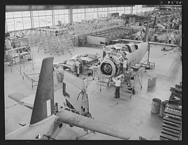 "Production. A-31 (""Vengeance"") dive bombers. Motor installation. A high angle view of a group of workers installing the motor on a Vultee ""Vengeance"" dive bomber at the Nashville Division of Vultee Aircraft Inc. Note that the inner wings are ready to be attached at this point. The ""Vengeance"" (A-31) was originally designed for the French. It was later adopted by the RAF (Royal Air Force) and still later by the U.S. Army Air Forces. It is a single-engine, low-wing plane, carrying a crew of two men and having six machine guns of varying calibers"