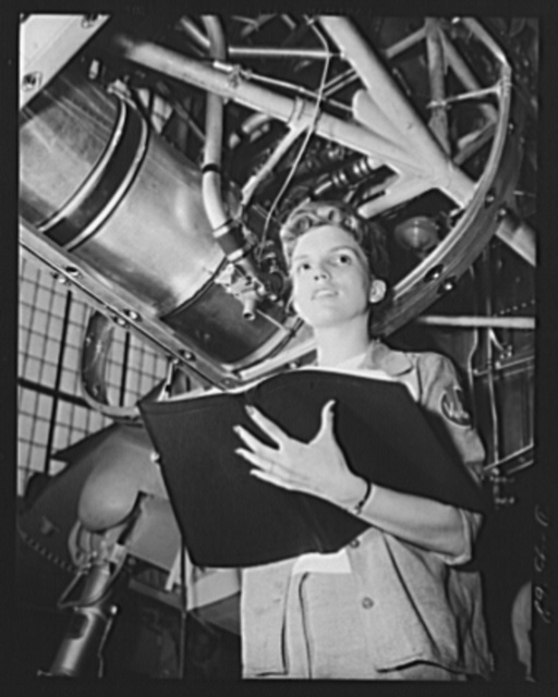 "Production. A-31 (""Vengeance"") dive bombers. She'd pass for a choir singer. A Vultee woman employee shown making a labor distribution check. She is standing under the engine nucleus of the ""Vengeance"" dive bomber manufcatured at Vultee's Nashville Division. The ""Vengeance"" (A-31) was originally designed for the French. It was later adopted by the RAF (Royal Air Force) and still later by the U.S. Army Air Forces. It is a single-engine, low-wing plane, carrying a crew of two men and having six machine guns of varying calibers"
