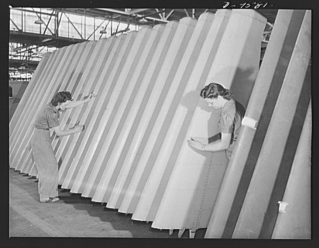 "Production. A-31 (""Vengeance"") dive bombers. Vertical stabilizer inspection. Women inspectors are shown inspecting the vertical stabilizers upon receipt from the sub-contractor prior to installation on ""Vengeance"" dive bombers made at Vultee's Nashville Division. The ""Vengeance"" (A-31) was originally designed for the French. It was later adopted by the RAF (Royal Air Force) and still later by the U.S. Army Air Forces. It is a single-engine, low-wing plane, carrying a crew of two men and having six machine guns of varying calibers"