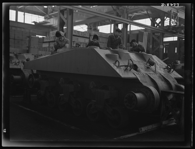 Production. M-4 tanks. Arc welders work on the partly-completed hull of a new M-4 tank at the Schenectady, New York, plant of the American Locomotive Company. M-7 mobile howitzer carriages are also produced in this plant