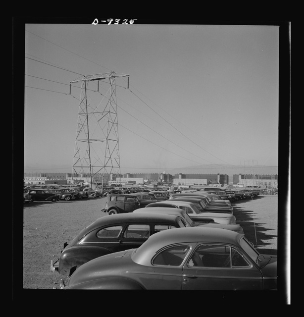 Production. Magnesium. Workers' cars parked under a section of the high-tension transmission lines which bring electrical power to Basic Magnesium's huge plant in the southern Nevada desert