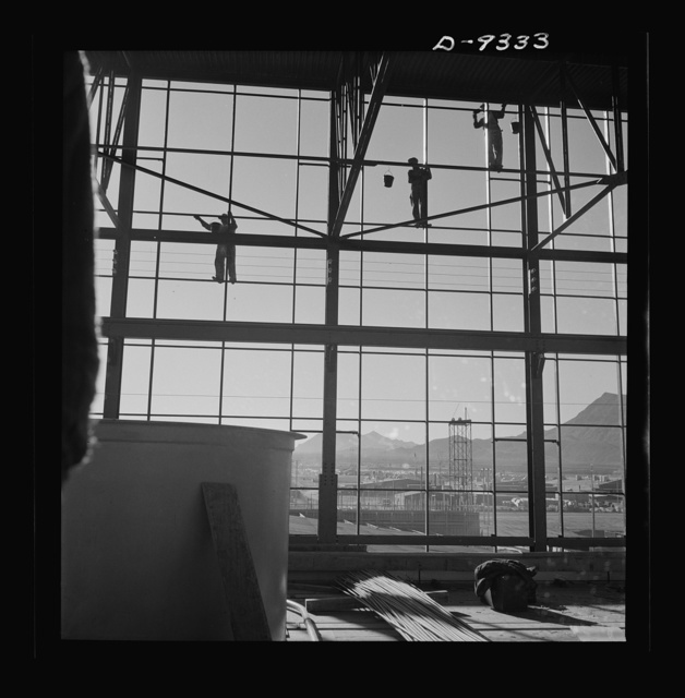 Production. Magnesium. Workmen seventy feet above ground are busily engaged in adding to the already gigantic proportions of Basic Magnesium's plant in the southern Nevada desert. A 24-hour production schedule results in turning out great quantities of magnesium for aircraft and tracer bullet manufacturers