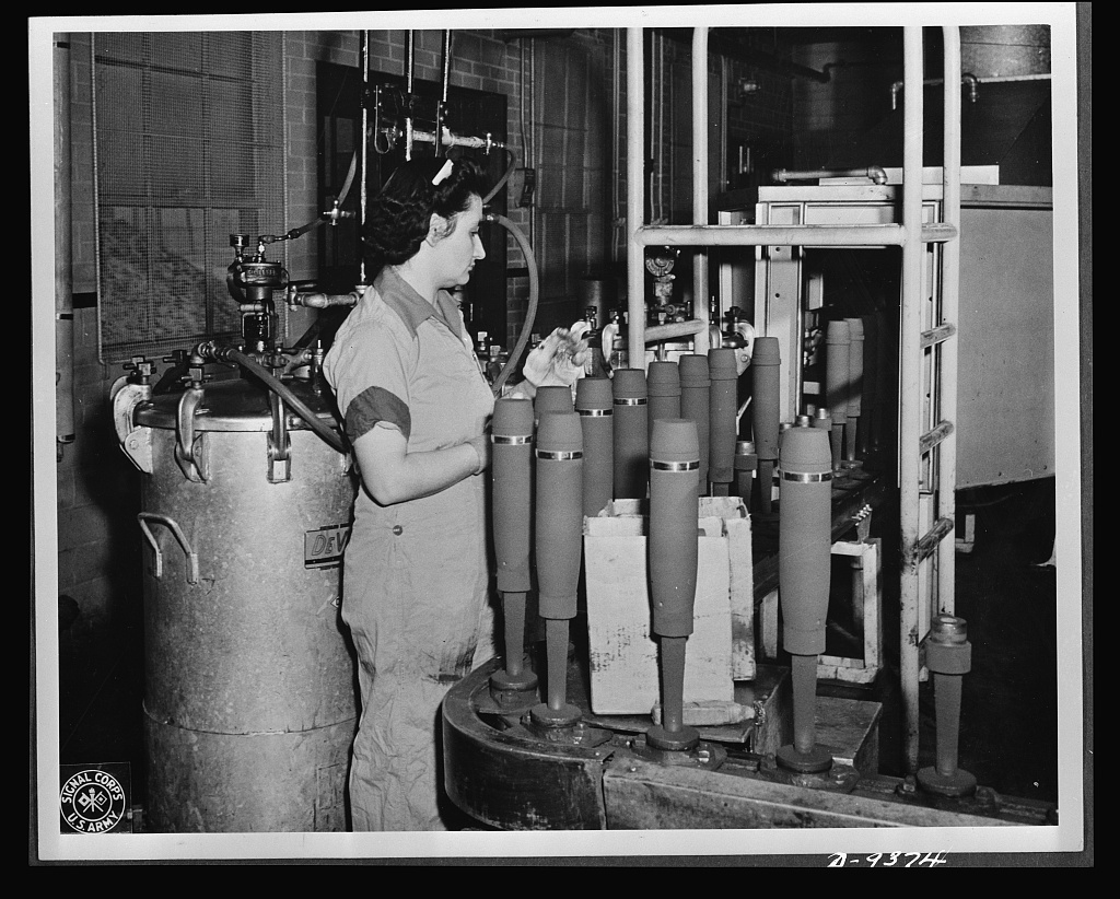 """Production. Shell loading. On the """"firing line"""" of a large Midwest loading plant, artillery shells soon to batter the Axis are sprayed with olive drab paint. This women is a sprayer, but women also do the """"puddling"""" of TNT in shells better than men. For """"puddling,"""" the stirring and packing of TNT in shells, is done much as a housewife prepares dough for cake. Ravenna ordnance plant"""
