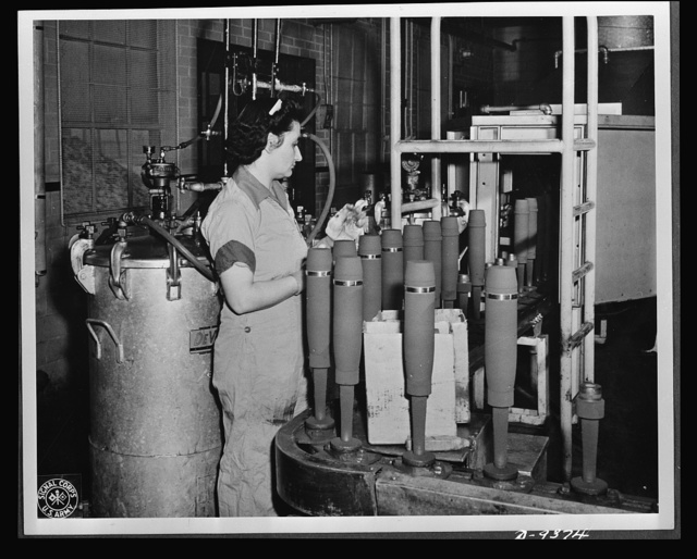 "Production. Shell loading. On the ""firing line"" of a large Midwest loading plant, artillery shells soon to batter the Axis are sprayed with olive drab paint. This women is a sprayer, but women also do the ""puddling"" of TNT in shells better than men. For ""puddling,"" the stirring and packing of TNT in shells, is done much as a housewife prepares dough for cake. Ravenna ordnance plant"