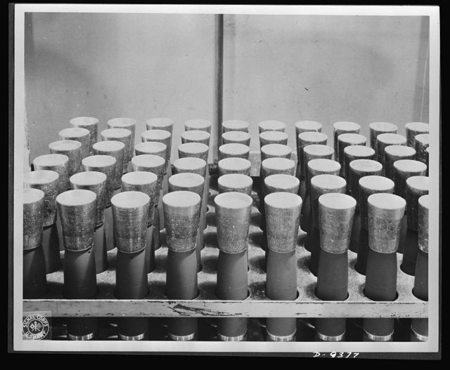 Production. Shell loading. TNT is poured into shells through these funnels on a distribution line in a large Midwest loading plant. TNT, used almost exclusively in shells, looks like a good grade of maple sugar. It is believed that soon the United States will use only TNT in bombs also. Ravenna ordnance plant