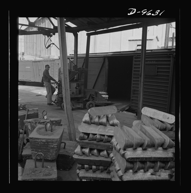 """Production. Zinc. Lead in the forms of pigs and of """"jumbo-blocks"""" being loaded on railway cars at a large smelting plant. From the Eagle-Picher plant near Cardin, Oklahoma, come great quantities of zinc and lead to serve many important purposes in the war effort"""