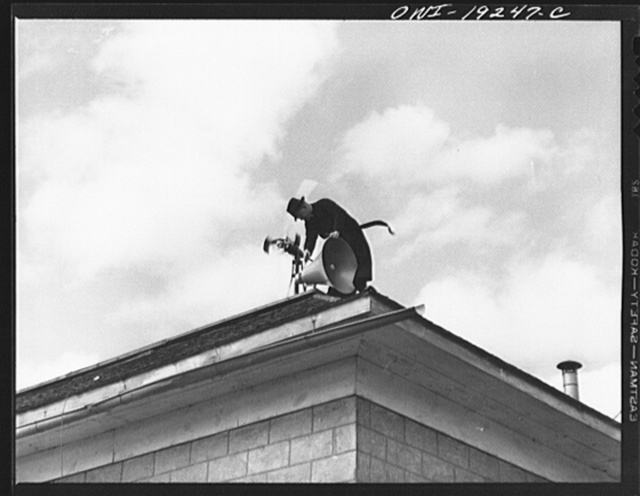 Questa, New Mexico. Father Smith adjusting his loudspeakers on top of the Questa parish house, where he daily broadcasts to the people