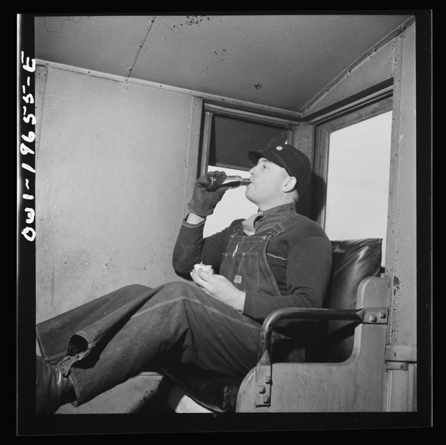 Rear brakeman George Clark having his lunch in the cupola of the caboose on the Atchison, Topeka, and Santa Fe Railroad, between Marceline, Missouri and Argentine, Kansas. The bottle contains hot coffee